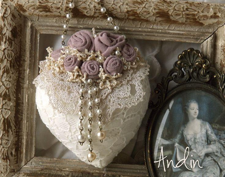 Srdíčko ve stylu Shabby chic Srdíčko je z jemné smetanové krajky. Zdobeno je sedmi ručně tvořenými růžičkami v šeříkové barvě, krémovými krajkami, a perličkovými přívěsky. Řetízek s perličkami jako závěsné poutko 11 x 13 cm + poutko