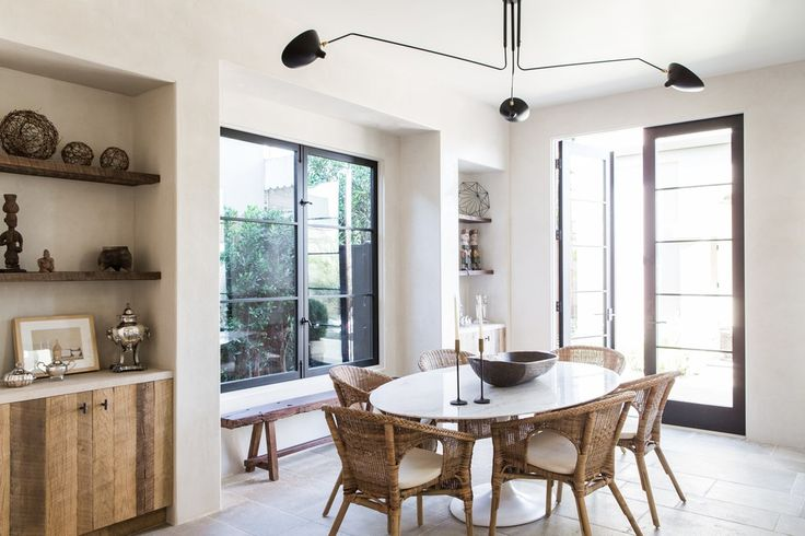 Saarinen table with Ikea rattan chairs and a Serge Mouille ceiling light. - Leigh Herzig