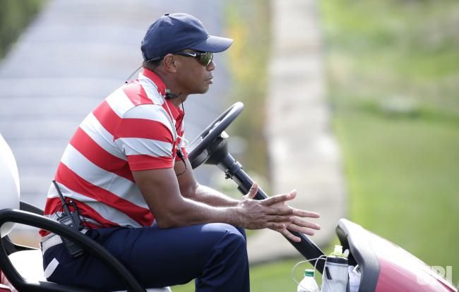 Assistant captain Tiger Woods of the United States sits in a golf cart at a practice round 2 days before the start of the Presidents Cup on…