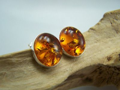 A fine pair of oval amber stud earrings in a cognac colour, mounted in silver 925