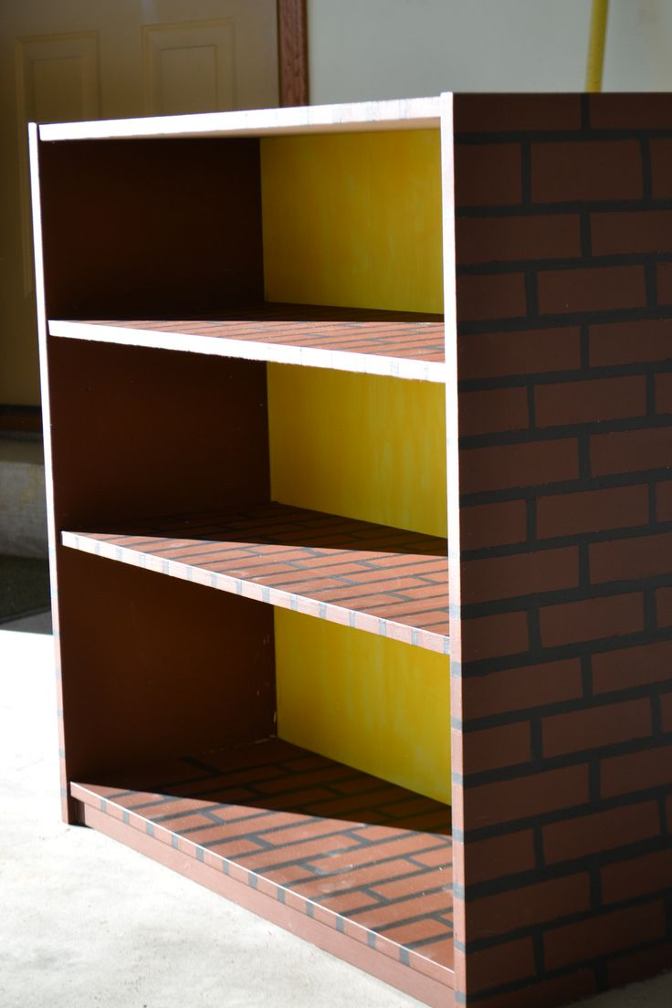 Mario brick bookshelf | Cheap bookshelf from walmart -sanded, primed, and painted. Made the lines using painters tape. Painted the cardboard backing yellow.