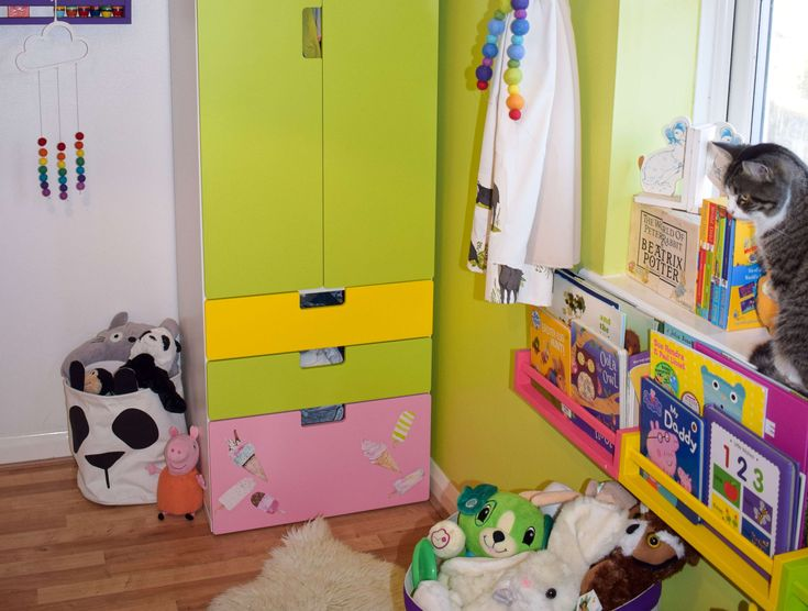 Rainbow themed toddler bedroom with panda accessories, ice cream decals, Ikea spice rack bookshelves and pom pom curtain tie backs
