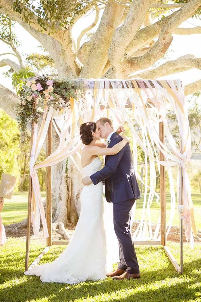 Arche de mariage faite de rubans en dentelle et d'une petite touche florale pour une cérémonie laïque en plein air.