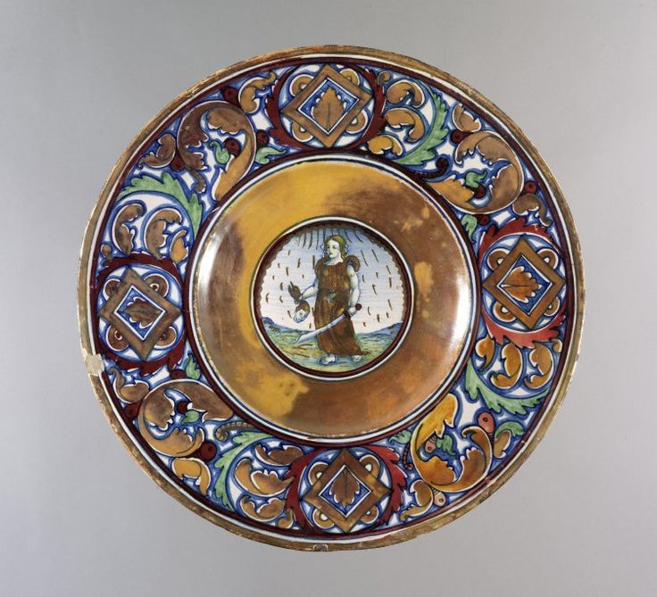Plate, warped rim, well curves to slightly convex centre. Underside is concave within the base. Earthenware covered front and back with a presumed tin-glaze. Front has painted decoration lustred in orange-brown and red. On the rim a pattern of foliage and fruit, and lustred diamonds. In the centre Judith holding the head of Holofernes. Reverse has seven concentric rings and a profiled head in lustre.