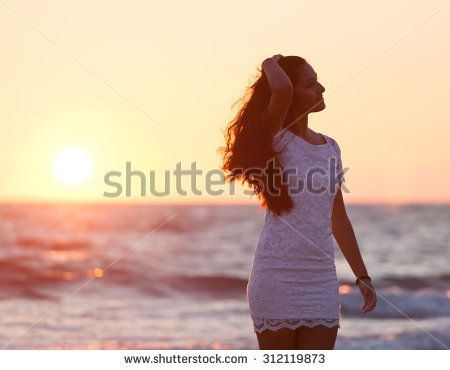 Beautiful young teenager with a white dress on the beach at sunset.