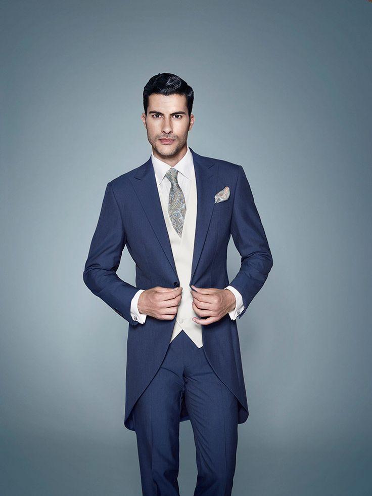Chaqué inglés para novio azul LORETO combinado con el chaleco semicruzado crudo y la corbata con estampado de fantasía.