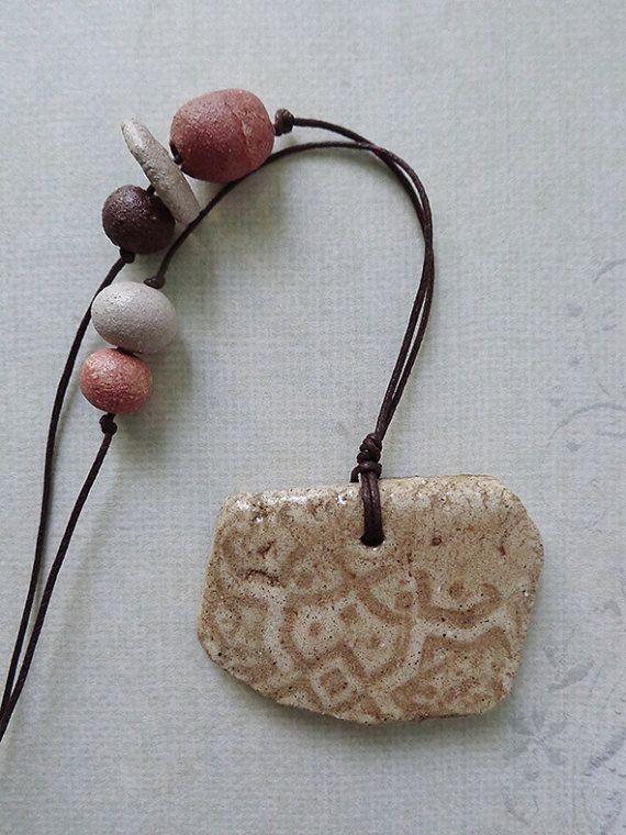 Beige ceramic handmade pendant necklace with imprint.