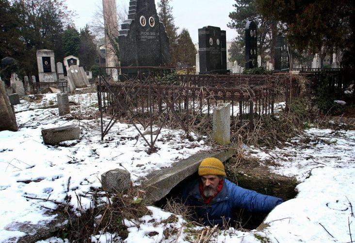 Un indigente, Bratislav Jovanovic, de 43 años, entra a una tumba que usa como refugio de invierno en el cementerio de Nis, a 200 kilómetros al sur de Belgrado (Serbia). (AFP/VANGUARDIA LIBERAL)