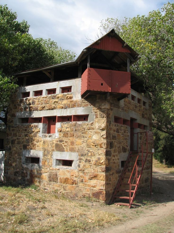 """1901 South Africa during the Anglo-Boer War. They were built by the British to protect the railway bridges from Boer attacks. The stone is local while the remaining materials were imported from Britain. These Blockhouses could house 20 men with water, ammunition and supplies stored on the lower floor. The """"living"""" area was the middle floor and was accessible by a retractable ladder and the top floor was the """"look-out"""" deck. Only 1000 of these Blockhouses were built."""