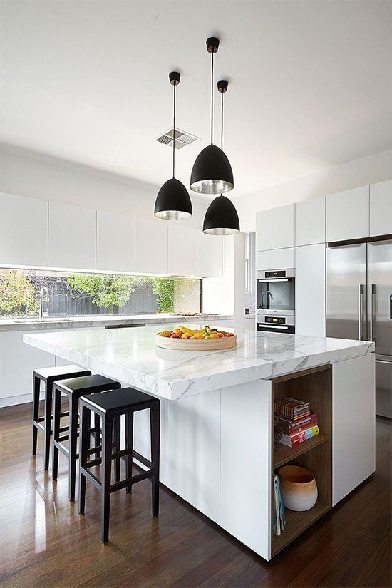 Contemporary white kitchen with white marble countertops, black kitchen barstools and several black pendant lights.