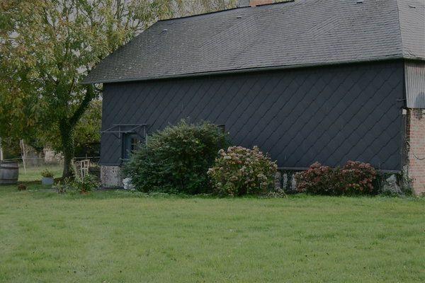 L'arrière de la maison repeint s'harmonise avec la toiture en ardoise gris anthracite.