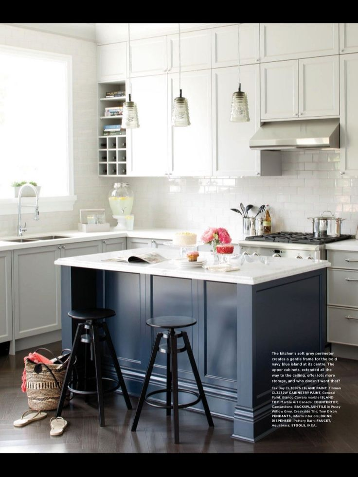 Soft grey lower cabinets create a more gentle introduction to a navy blue island, rather than the sharp white