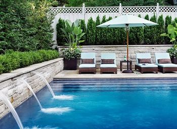 Beautiful pool with retaining wall with shrubs and acting as water falls.