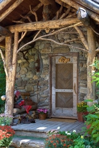 Rock house with small trees with branches intact as supports on the porch.