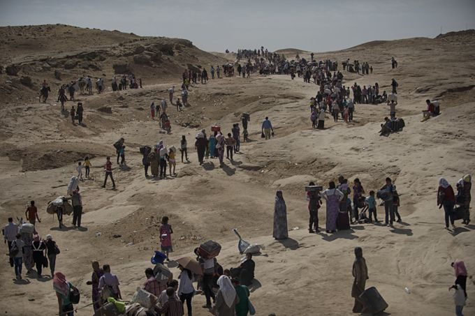 Thousands of Syrian refugees cross from Syria into the Kurdish region of northern Iraq near the Peshkhabour border point in Dohuk, Iraq. Ira...