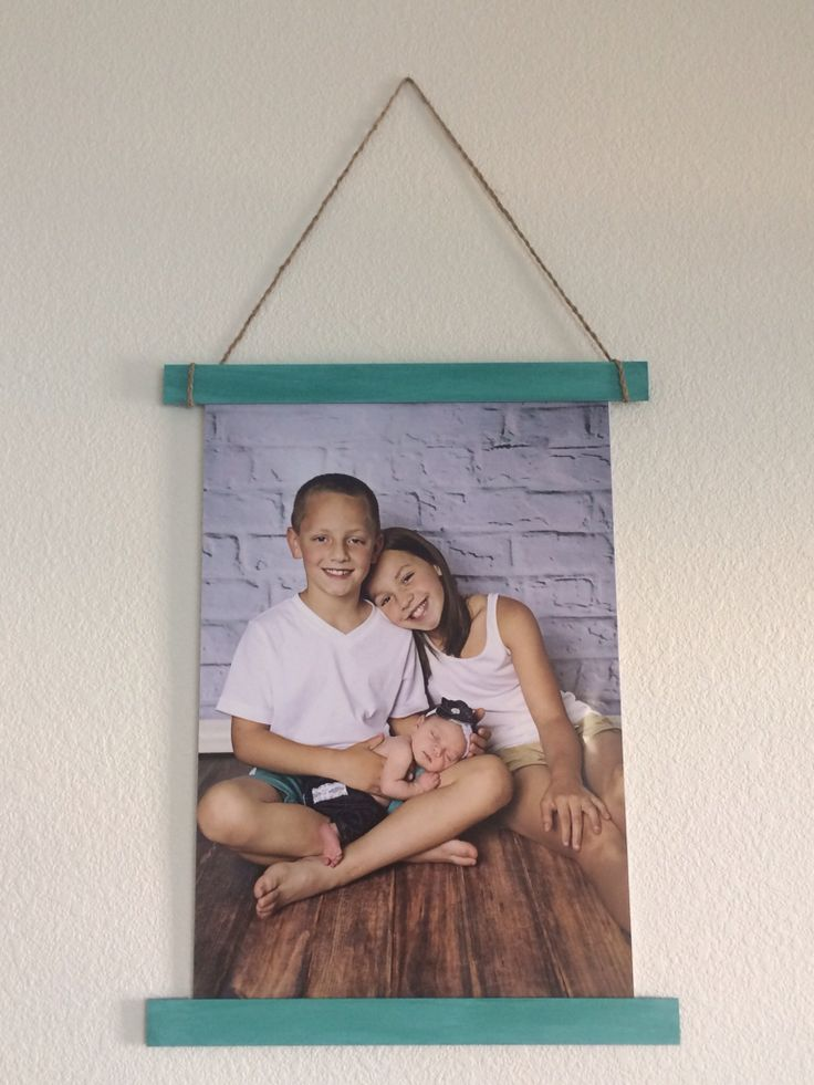 """Had a poster made of the grandkids and really dislike the cheap poster frames but didn't want to spend a lot of $$ so I simply stuck the 20""""x30"""" poster on 20""""x30"""" foam board with mod podge, painted a couple of slats of wood and actually taped the foam board onto the slats and braided some string I had on hand for the hanger and BINGO! DONE!"""