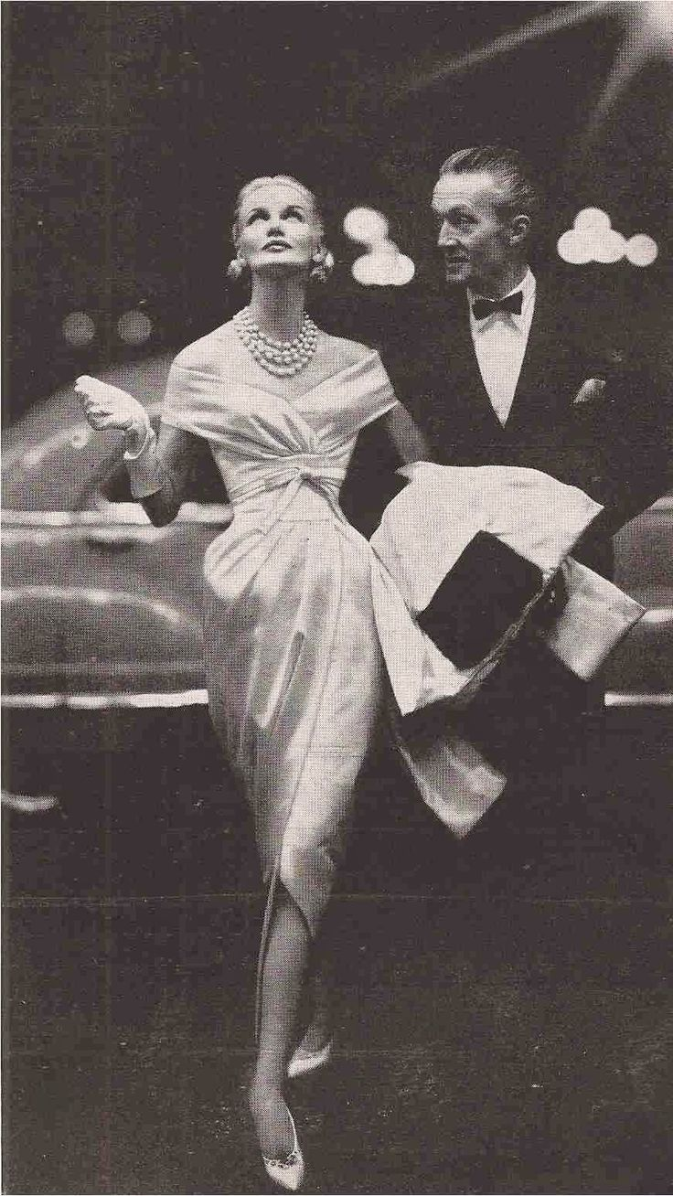 Givenchy's shoulder-banding white satin dress with tapered slashed skirt and a satin shawl is threaded with mink, 1954
