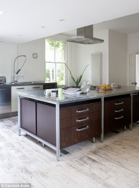 The contemporary kitchen dark-laminate and stainless-steel units are by Boffi (boffi.com), and have been topped with hard-wearing granite and limestone