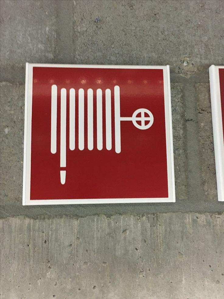 Vlak - Deze afbeelding van een brandslang wordt geïllustreerd op een rood vlak. Dit vlak heeft een witte dikke rand. Deze rand kan ook als een achterliggend vlak bezien worden.