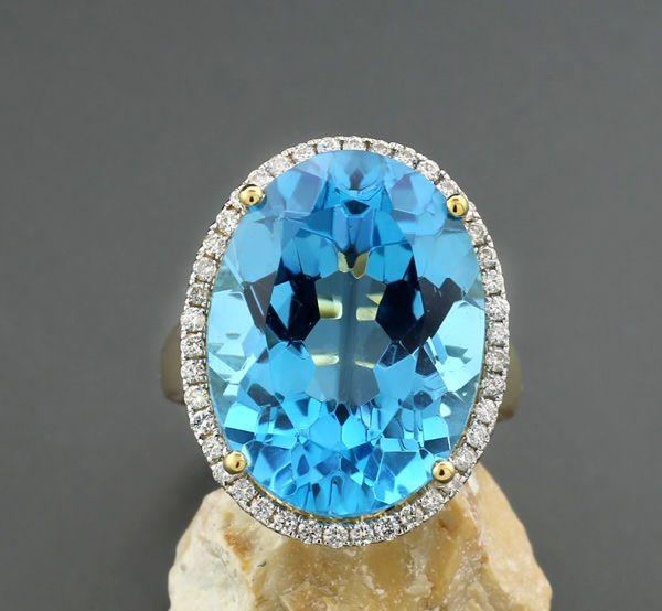 """Blauwe topaas briljante ring totale ring breedte: 55. 2258 karaat Zwitserse blauw 750 geel goud - geen minimumverkoopprijs  Een ovale gefacetteerde blauwe topaas van ca. 22.20 ct lichtgevende levendig blauw zogenaamde """"Zwitserse blauw"""" set à jour (blauwe topaas verwarmd als markt standaard) enigszins verlaagd rhodinated frame set rondom met 42 brilliants van ca. 0.38 ct in totaal Wesselton / SI-P1. De iets toelopende ring wand heeft een lancet patroon. Gemaakt in 750 / 18 kt geel goud…"""