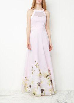 Pearly Petals maxi-jurk van Ted Baker, vervaardigd uit een transparante kwaliteit in lichtroze. Het mouwloze model is voorzien van een ronde halslijn, een opening aan de achterzijde en een tailleband. Verder is de onderzijde van de elegante jurk uitgevoerd in een bloemenprint. Het ontwerp is daarbij uitgerust met een voering en een blinde ritssluiting aan de achterzijde.