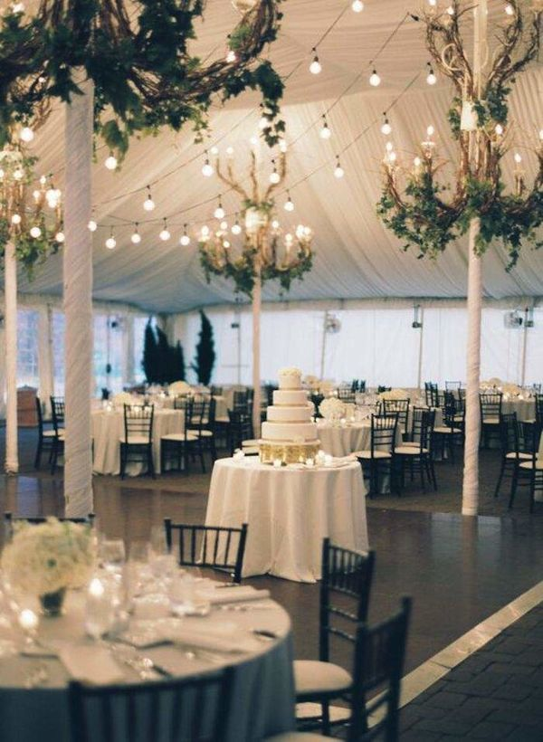 Upgrade your tented wedding venue by decorating its poles with ribbon and using hanging wedding decor to give it a more polished appearance.