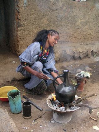 Ethiopia: - coffee ceremony by the type of her tradtional dress most-likely from Gonder or Wolo region