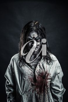 Portrait of the horror zombie woman with bloody face against the black background