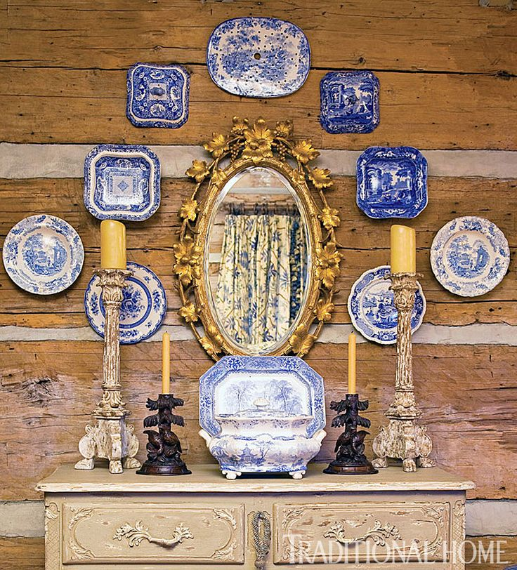 Antique blue-and-white china plates and a gilded mirror hang on rough-and-tough log walls. - Photo: Jenifer Jordan/ Design: Charles Faudree