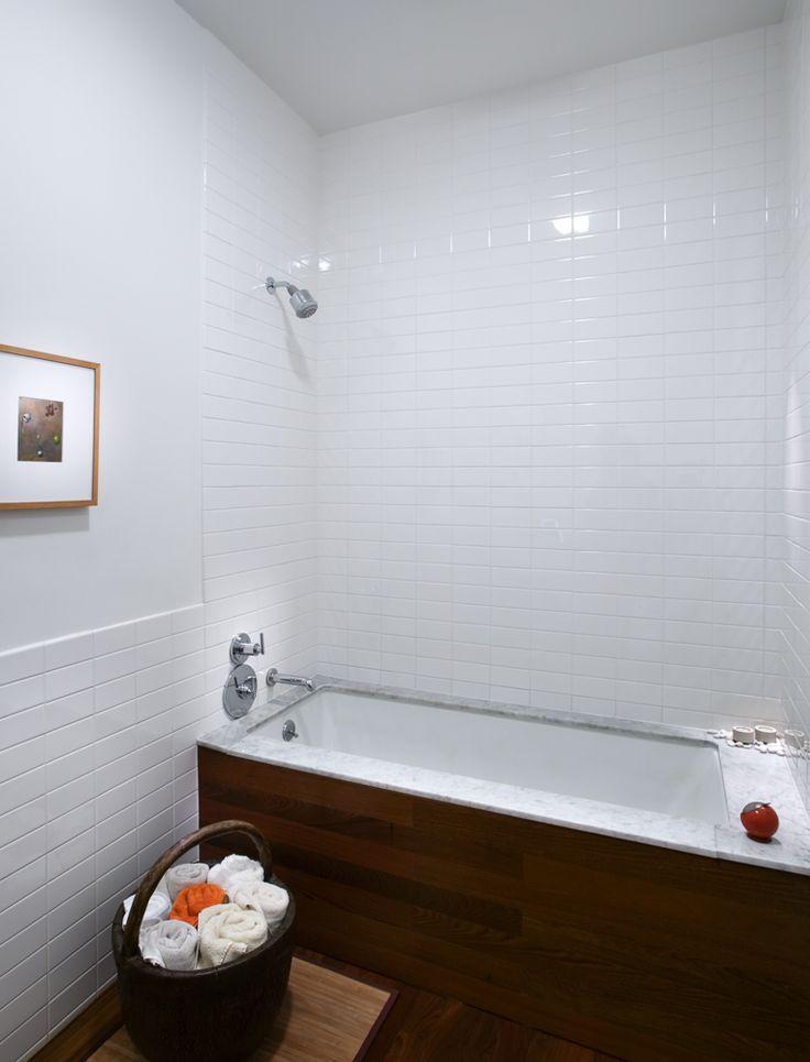 Bathroom Ipe wood floors and tub apron. Marble tub deck over undermount tub. Stack bond white subway tiles