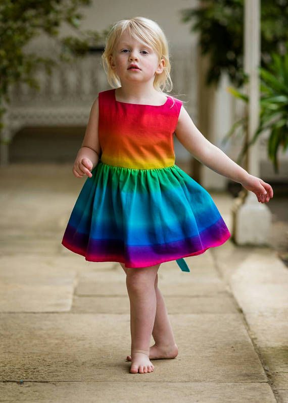 This beautiful rainbow party dress is made from soft cotton and is fully lined in lawn. This retro style would make an adorable birthday dress, an epic party dress or wear it for any special occasion. Handmade with care in London by a third generation seamtress. Beautiful inside and out. Made with a 1950s vibe it has a full skirt attached to a neat sleeveless bodice. It buttons at the back with four sparkly pink buttons. The skirt should fall just on the knee (my 4 year old model wears the…