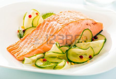 Gourmet oven-baked pink salmon steak served with thinly sliced..