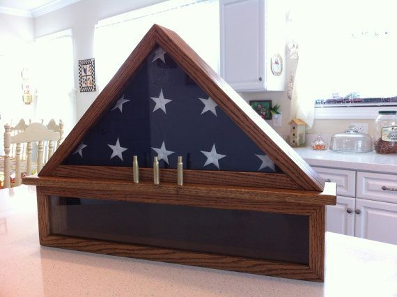 I handcraft custom flag display cases Sized for 5 X 9.5 burial flag Includes three shell casings (represents a 21 gun salute) Flag case sits on a 6 medals section used to display mementos, ribbons, patches Pictured in Oak wood with early american stain. Other wood types and stains available  Customer can also order this case in Walnut wood for $25 more. For this option, be sure to click on Create a custom order.  Customers asked to specify wood type (Cherry, Oak, Walnut), stain and velvet…