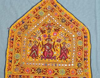 """A Ganesh Sthapana: an embroidered 5-sided shrine or temple cloth, depicting Ganesh, the elephant headed deity who signifies wisdom and the Remover of Obstacles. His blessings are invoked at every significant event. Here, Ganesh is flanked by his consorts, Siddhi (spirituality) and Riddhi (prosperity). The Ganesh Sthapna is a colorful meeting of sacred tradition and artistic freedom. by the Kanabi Farming caste of Saurashtra region of Gujarat. 22 1/2"""" x 21"""""""