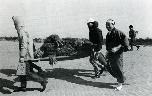 three men carrying a stretcher with godzilla on it