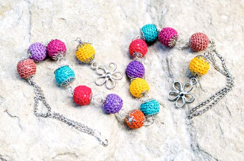 Original and bright youth set of large beads, braided with multicolored cotton thread. Each bead is decorated with a metal fittings of different shapes. Earrings also supplemented with metal pendants in the shape of flowers. Due to the unique texture of the product goes well with both warm pullo...