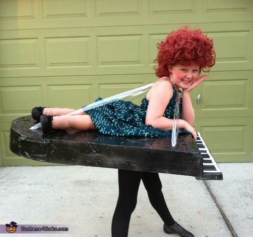 Renee: My daughter is standing with a wig on and the piano as you can see is just hanging from her shoulders. I made the piano out of foam board and...