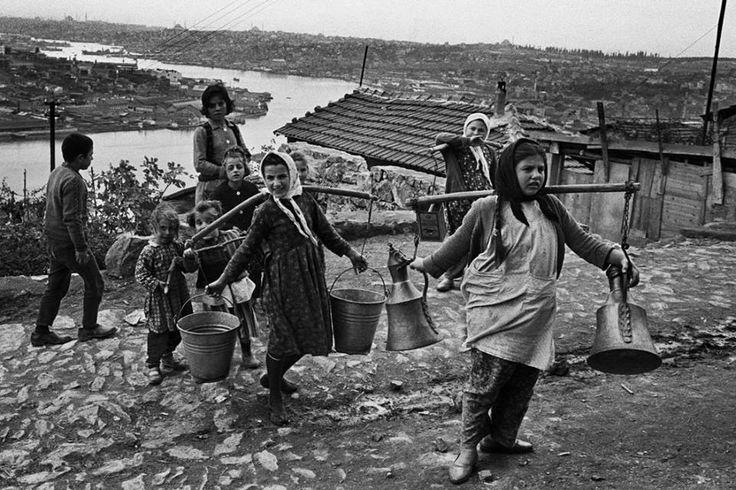 Gecekondulara taşınan su.   Çocukluk, garip bakışlar eşliğinde kovalardan dökülmede.  Eyüp, 1965.  The water that carried to shanties.  Eyup Istanbul, 1965