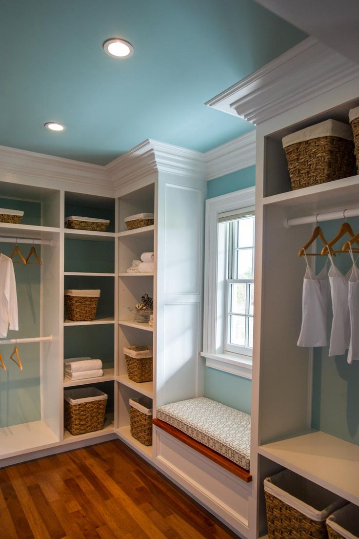 A cozy window seat separates custom-built closet units and offers a comfortable place to rest while getting ready.