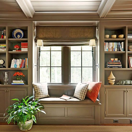 Paneled to Perfection  Green-gray hues, abundant paneling, and a low, coffered ceiling create cozy, cottagelike appeal in the family den. Built-in shelving and cabinets offer both open and closed storage, and a window seat invites readers to sit and stay awhile.