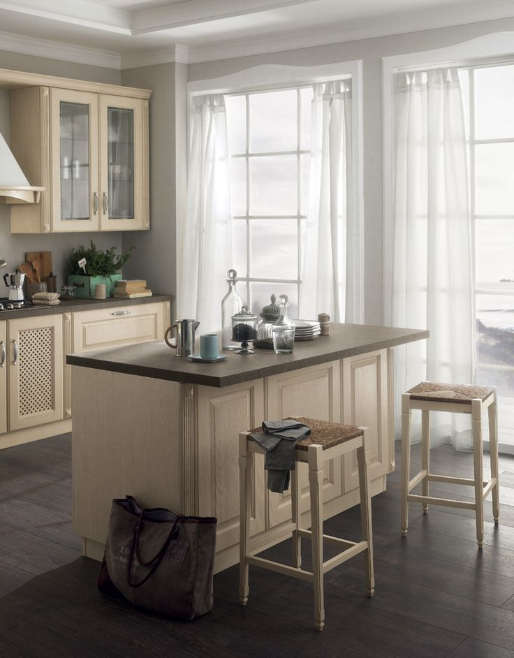 Featuring solutions which recall the kitchens of bygone days (the wooden gratings, the chimney-shaped hood and the moulded fronts), the Madeleine kitchen with Butter White Ash doors includes an island that meets today's needs for an intelligently furnished space that can be lived to the full.
