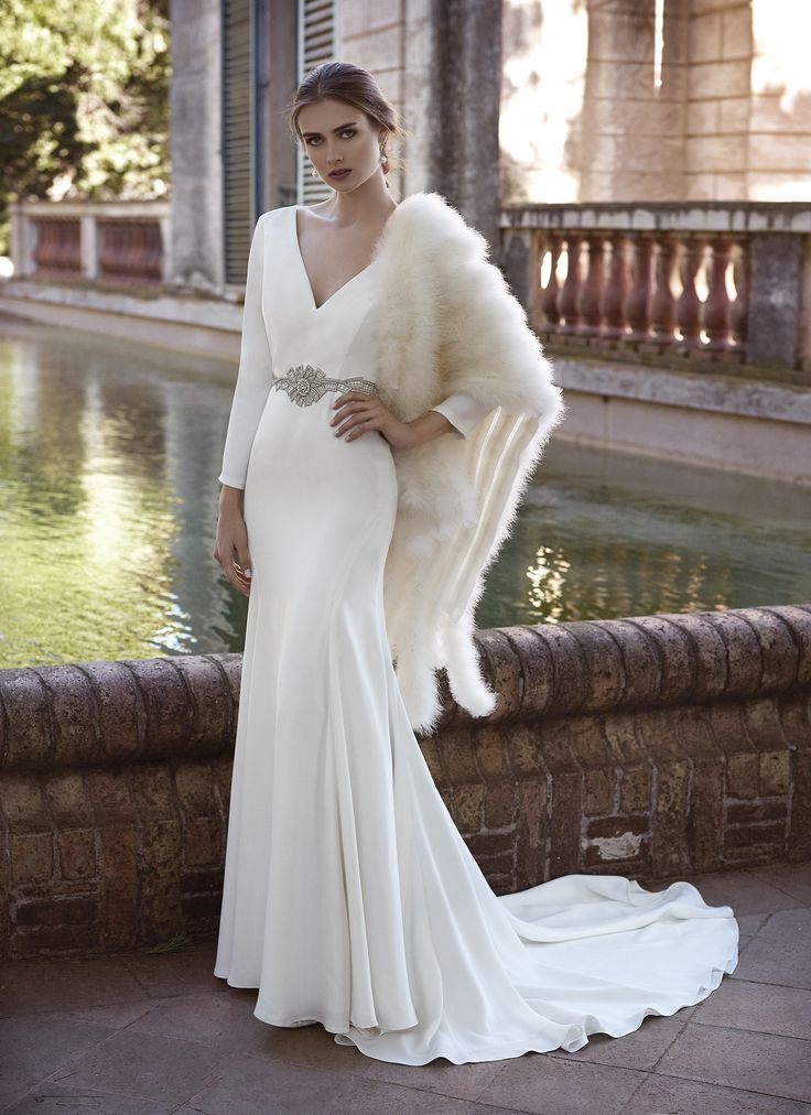 Espectacular vestido de novia de crepê, líneas puras, con cinturón de pedrería, manga larga y espalda con transparencias. Complemento de chal de plumas blanco marfil. Vestido novia de invierno.