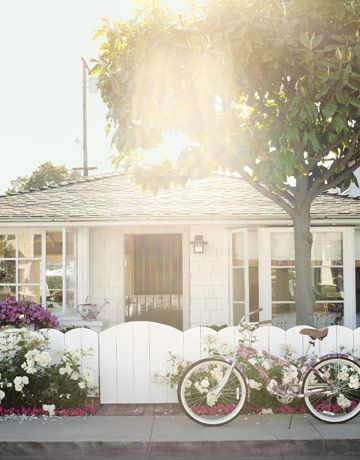 A Sunny Summer Home:     In front of the 1938 California cottage is a Liberty of London bicycle from Target; it belongs to designer Krista Ewart's sister Laurie Thiel, the home­owner.