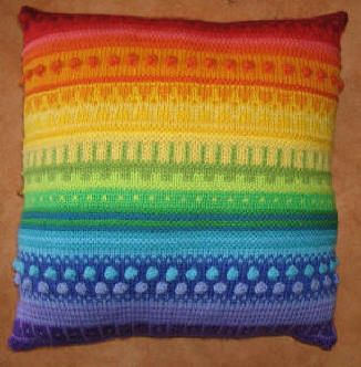 A knitted rainbow cushion. I'd love to have a set of these for my couch. :3