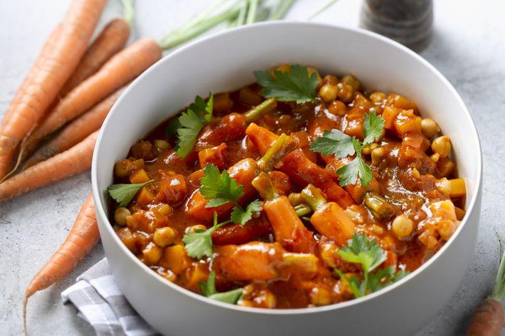 tajine - pompoen, kikkererwten, ... - Stoof de ui en knoflook aan in de olie. Voeg na 3 minuten de pompoen, de wortelen en de tomatenblokjes toe. Overgiet met de groentebouillon en kruid met de komijn, het kaneel en de chilivlokken. Laat afgedekt 30 minuten sudderen op een middelhoog vuur tot alle groenten beetgaar zijn.