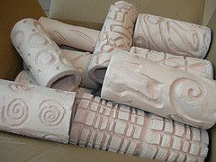 Carved clay cylinders that are bisque-fired.