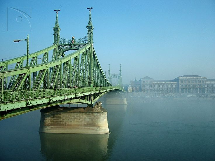 art-zane:    The Liberty Bridge and the University of Economics on a foggy day: The Liberty Bridge connects Buda and Pest across the River Danube. Liberty Bridge was built between 1894 and 1896 and originally named after the Emperor Franz Joseph I of Austria who personally opened the bridge by hammering the last silver rivet on the Pest abutment. The bridge imitates the general outline of a chain-type bridge which was considered an aesthetically preferable form at the time of its…