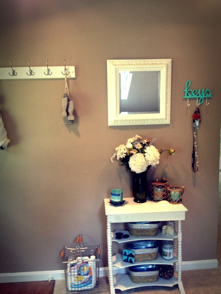 Small apartment entryway. Hooks for keys, small table for mail, shoes can go under, mirror above