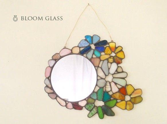ガラスのモザイクミラー サイズ横x縦:20.5cm x 18.5cmミラーのみのサイズ横x縦:10.5cm x 10.5cmステンドグラスのミラーです。様々な色のガラスを集め、おはなの形にまとめました。色の配色やガラスの素材はすべて1点1点異なります。お気に入りを見つけていただければうれしいです◎白い壁に吊るしてもらうとガラスの色が映え、とてもキレイです。-------------------------------------------------※作品は、既製の段ボール素材の小箱にお入れし、クッション材には新聞紙などを使用いたします。何卒ご了承くださいませ。※ラッピングは、上記の小箱に簡単な飾りをお付けするものとなります。クッション材には、新聞紙は使用せずクラフト紙(茶色の無地の紙です)を使用いたします。ご希望の場合は、ご購入の際にメッセージにてお知らせくださいませ。※ガラスは光の加減により色味や雰囲気が変わって見えます。写真では伝わりづらいところもありますので、ご不明な点はお手数ですがお問い合わせください。ハンドメイド新作2017