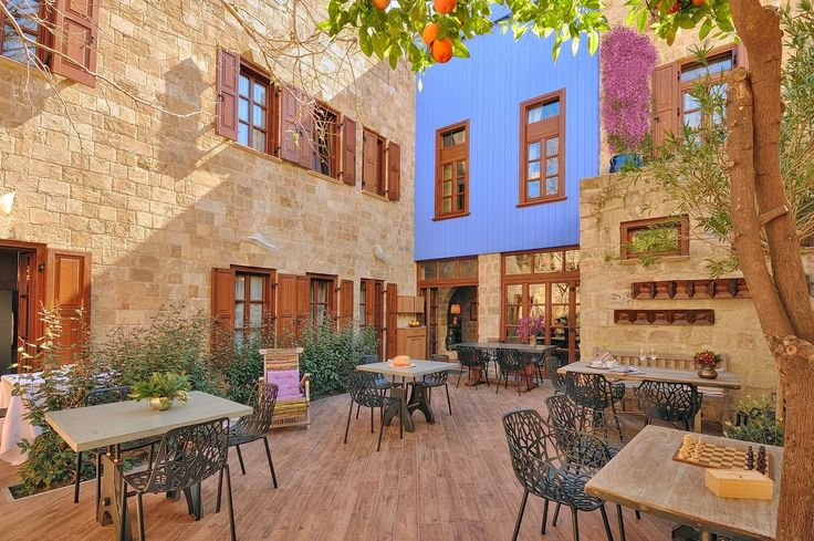 EXCLUSIVE SUITES BOUTIQUE HOTEL. MEDIEVAL TOWN, RHODES, GREECE. -  Part of the yard, with the blue wall, tangerines and one of our bouganvillas.  - kokkiniporta.com